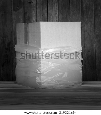 Brown recycle paper box in plastic bag lay down on wood floor and grunge wood panel as still life art with plenty room for copy black and white version - stock photo