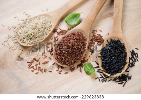 Brown, red and black rice kernels in wooden spoons, close-up - stock photo