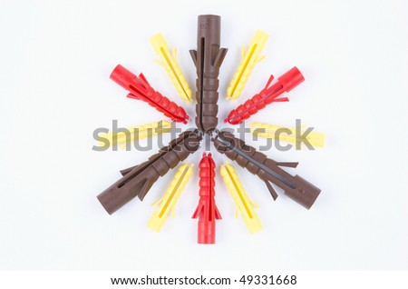 Brown, red and yellow wall plugs arranged in a star shape - stock photo