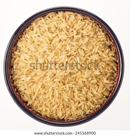 Brown rice in bowl isolated on white background - stock photo