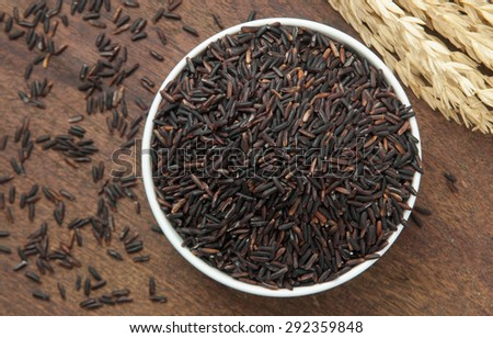 brown rice in bowl on wood table. - stock photo