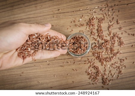 Brown rice in hand on wooden background.
