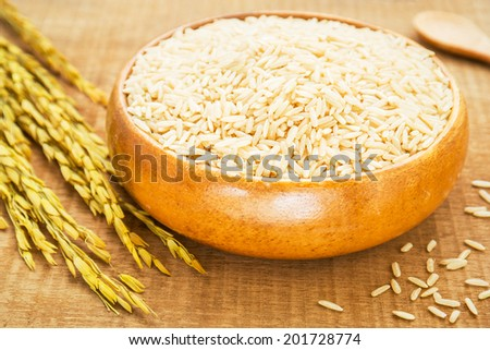 Brown rice in wooden bowl - stock photo