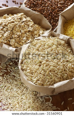 Brown rice, oatmeal, millet and buckwheat in paper bags.