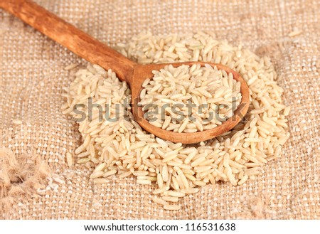 brown rice on sacking  in wooden  spoon