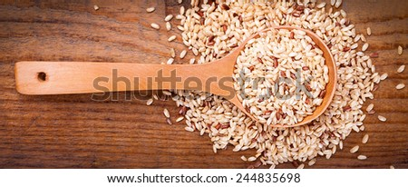 brown rice on spoons,on wooden background - stock photo