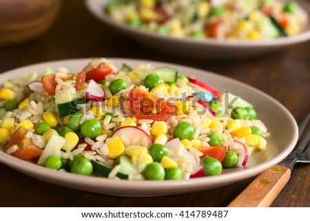 Brown rice salad with cherry tomato, corn, cucumber, radish and peas served on plate, photographed on dark wood with natural light (Selective Focus, Focus one third into the salad)