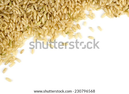Brown rice scattered against white with copyspace - stock photo