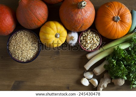 Brown rice, various types of winter squash, leeks , pine nuts and garlic from above with copy space, a healthy eating still life - stock photo