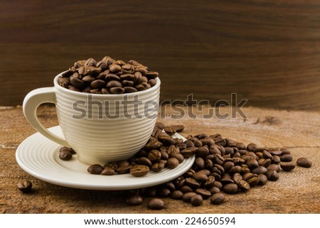 Brown roasted coffee beans in coffee cup on wood.