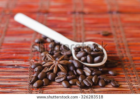 Brown roasted coffee beans, seed with spoon and spices. Espresso dark, aroma, black caffeine drink. Closeup isolated energy mocha, cappuccino ingredient.  - stock photo
