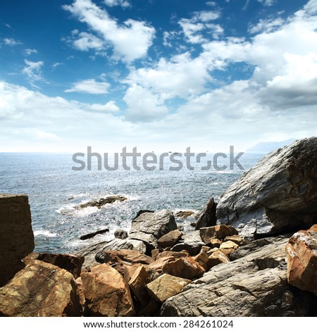 brown rocks and sea with blue sky