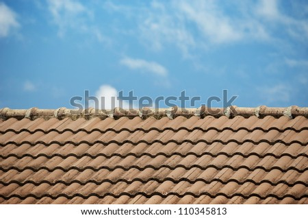 Brown roof tiles made from a ceramic material and the sky.
