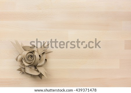Brown Rose Flower Paper Ribbon on the Wood Table or Desk Background Copy Space on the Top Right  / Eco Friendly Material from Nature  - stock photo