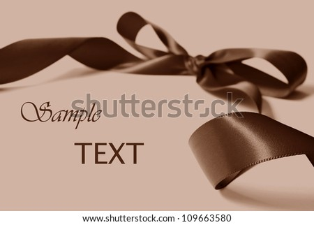 Brown satin ribbon on a beige background with copy space.   Macro with extremely shallow dof. - stock photo