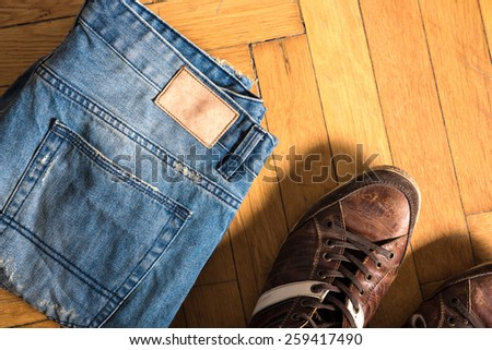 Brown shoes and blue jeans lie by on the floor.  - stock photo
