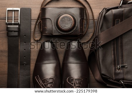 brown shoes, belt, bag and film camera on the wooden table - stock photo