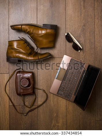 brown shoes, belt, bag and film camera with tablet computer - stock photo