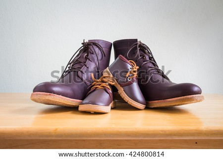 Brown shoes of daddy and son on on wooden table, bar or counter over white wall background, fathers day   - stock photo