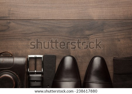 brown shoes, socks, belt, and film camera on wooden table - stock photo