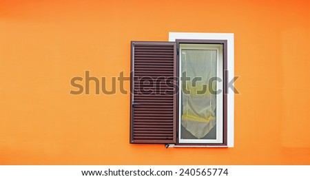 brown shutters in an orange wall - stock photo
