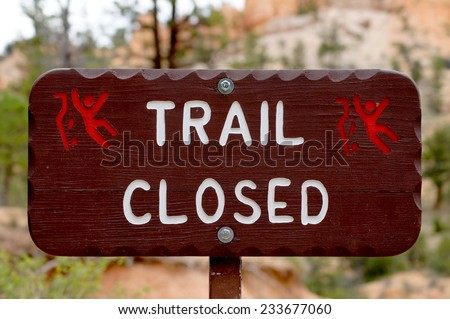Brown sign warning about the danger of a closed footpath in a national park. - stock photo