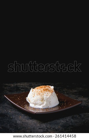 Brown square ceramic plate with homemade vanilla ice cream, served with coconut flower sugar over black table - stock photo