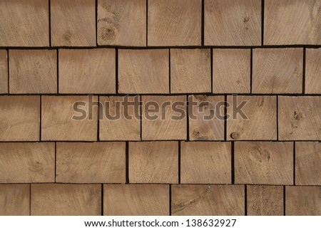 Brown stained cedar shingle from a wall. Background and texture.