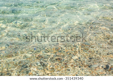 Brown stone in clear sea water - stock photo