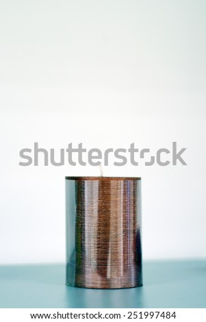 Brown stylish round candle with white wick stands on green table - stock photo