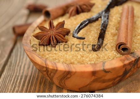 Brown sugar, anise, vanilla and cinnamon in a wooden bowl on a brown background - stock photo