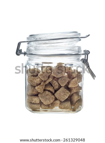 Brown sugar cubes in a glass jar isolated - stock photo