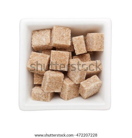 Brown sugar cubes in a square bowl isolated on white background