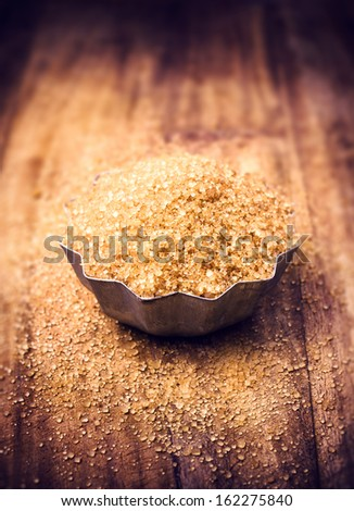 Brown sugar for a Christmas baking in a bowl on wooden table, selective focus.  - stock photo