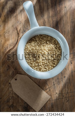 brown sugar in a bowl on wooden background with a blank label next
