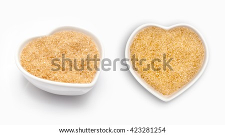 Brown sugar  in a heart shaped bowl, isolated on white - stock photo