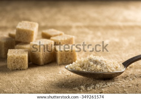 Brown sugar in spoon and sugar cubes - stock photo