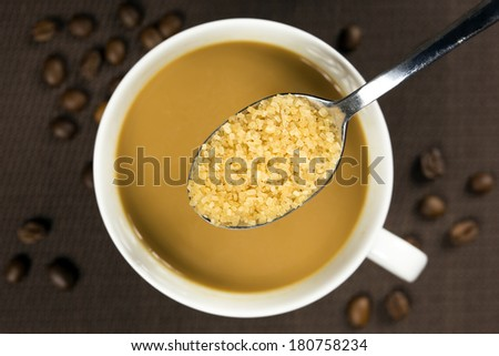 Brown sugar on a spoon and a cup of coffee underneath - stock photo