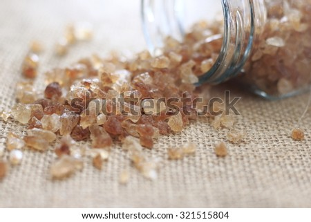 brown sugar rock organic crystalline on jute cloth in glass bottle
