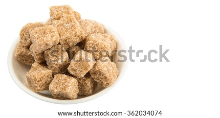 Brown sugarcane cube in white bowl over white background