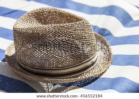 Brown summer male straw hat on beach towel, vacation relax moment on holidays