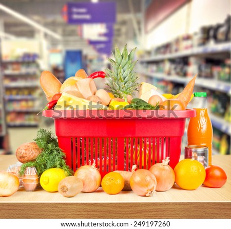 Brown table and on background blured supermarket and basket with products - stock photo