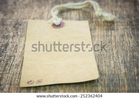 Brown tag isolated on wood background - stock photo