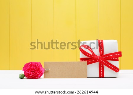 Brown Tag with Attractive Carnation Flower and Gift Box with Ribbon on Yellow Wooden Wall Background - stock photo