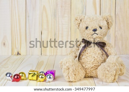 brown teddy bear with Gift box on wood background, concept Merry christmas and new year