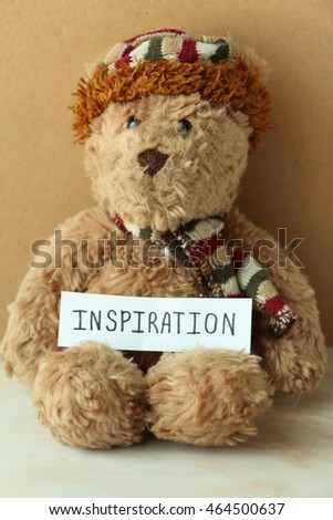 Brown teddy bear with paper writing inspiration.