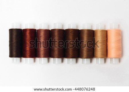 brown thread of different shades. Spools of thread.