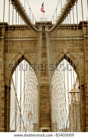 brown toned detail photo of Brooklyn Bridge in New York City, waving American flag - stock photo