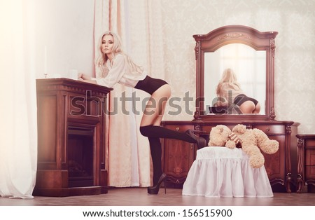 brown toning picture of lovely young woman in sexy outfit posing in luxury interior - stock photo