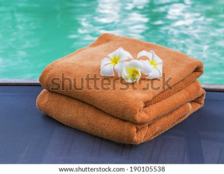 Brown towels and frangipani near swimming pool  - stock photo